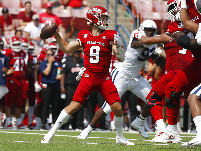 Fresno State quaterback Jake Haener throws a pass past Connecticut defenders during the first half of an NCAA college football game in Fresno, Calif., Saturday, Aug. 28, 2021. (AP Photo/Gary Kazanjian)