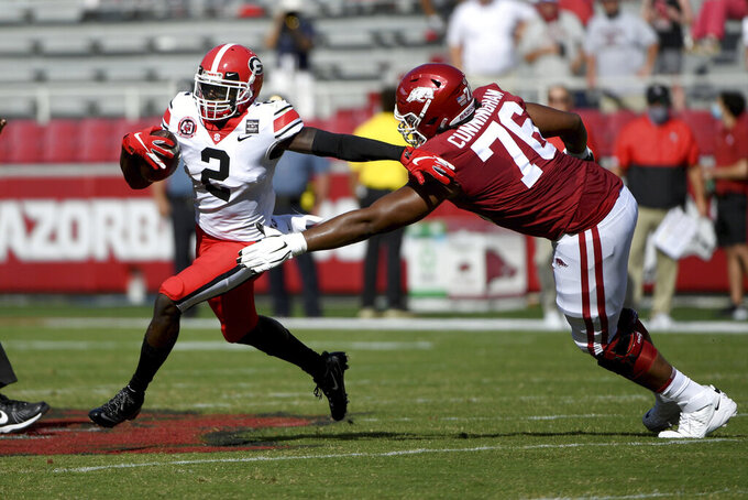 Georgia defensive back Richard LeCounte (2) runs past Arkansas lineman Myron Cunningham (76) as he returns an interception during the first half of an NCAA college football game in Fayetteville, Ark., Saturday, Sept. 26, 2020. (AP Photo/Michael Woods)
