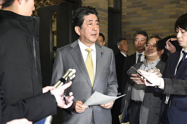 Japanese Prime Minister Shinzo Abe, center, speaks to reporters at his official residence in Tokyo Sunday, Jan. 26, 2020. Abe said he is making arrangements to fly Japanese people home from the Chinese city of Wuhan, hit by an outbreak of a new virus recently. (Mizuki Ikari/Kyodo News via AP)