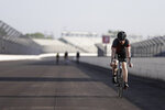 IndyCar driver Charlie Kimball rides his bicycle down the main straightaway at Indianapolis Motor Speedway, Sunday, May 24, 2020, in Indianapolis. The Indianapolis 500 was postponed because of the coronavirus pandemic. The race will instead be held Aug. 23, three months later than its May 24 scheduled date. (AP Photo/Darron Cummings)