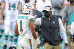 FILE - Miami Dolphins head coach Brian Flores talks to quarterback Tua Tagovailoa (1) on the sidelines as the Dolphins play against the Los Angeles Chargers during an NFL football game in Miami Gardens, Fla., in this Sunday, Nov. 15, 2020, file photo. The San Francisco 49ers have made a big move to grab their quarterback of the future by trading up with Miami for the No. 3 pick in next month's draft. For the Dolphins, the trade signals they're not in the market for another potential franchise quarterback, and will stake their future on Tua Tagovailoa. (AP Photo/Doug Murray, File)