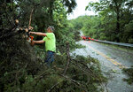 Tony Brinker, a volunteer with the Augusta Fire Protection District, cuts trees that were blocking Highway 94, Tuesday, May 21, 2019, near Augusta, Mo. A long north-south line of storms hit the St. Louis area Tuesday evening. The storms are part of a weather system moving across the Midwest that began last weekend and will continue through the week, according to the National Weather Service. (David Carson/St. Louis Post-Dispatch via AP)
