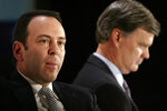 FILE- In this Nov. 17, 2004, file photo Kmart chairman Edward Lampert, left, and Sears CEO Alan Lacy listen during a news conference to announce the merger of Kmart and Sears in New York. A bankruptcy judge has blessed a $5.2 billion plan by Sears chairman and biggest shareholder Lampert to keep the iconic business going. The approval means roughly 425 stores and 45,000 jobs will be preserved. (AP Photo/Gregory Bull, File)