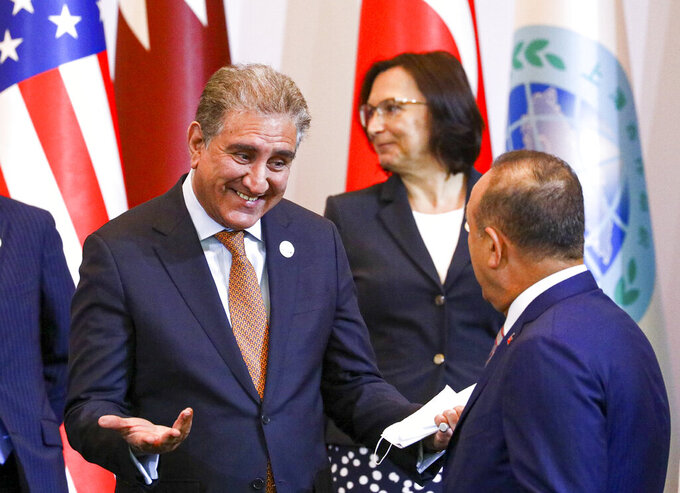 CAPTION CORRECTS THE ID - In this handout photo released by Russian Foreign Ministry Press Service, Pakistan's Foreign Minister Shah Mahmood Qureshi, left, gestures while speaking to Turkish Foreign Minister Mevlut Cavusoglu, right back to a camera, prior to a Central and South Asia 2021 conference in Tashkent, Uzbekistan, Friday, July 16, 2021. (Russian Foreign Ministry Press Service via AP)