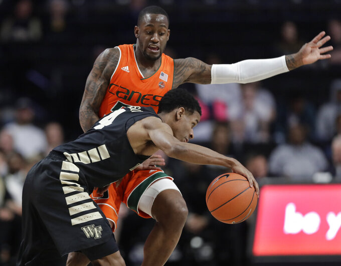 Wake Forest's Torry Johnson, front, drives against Miami's Zach Johnson during the second half of an NCAA college basketball game in Winston-Salem, N.C., Tuesday, Feb. 26, 2019. (AP Photo/Chuck Burton)
