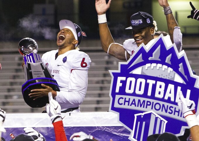 Fresno State quarterback Marcus McMaryion (6) celebrates with the Mountain West Conference Championship trophy after the team's 19-16 win over Boise State during an NCAA college football game for the Mountain West Conference championship Saturday, Dec. 1, 2018, in Boise, Idaho. (Darin Oswald/Idaho Statesman via AP)