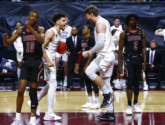Grand Canyon's Asbjørn Midtgaard, center, reacts with Gabe McGlothan, left, after scoring against New Mexico State during the second half of an NCAA college basketball game for the championship of the Western Athletic Conference men's tournament Saturday, March 13, 2021, in Las Vegas. (AP Photo/Chase Stevens)