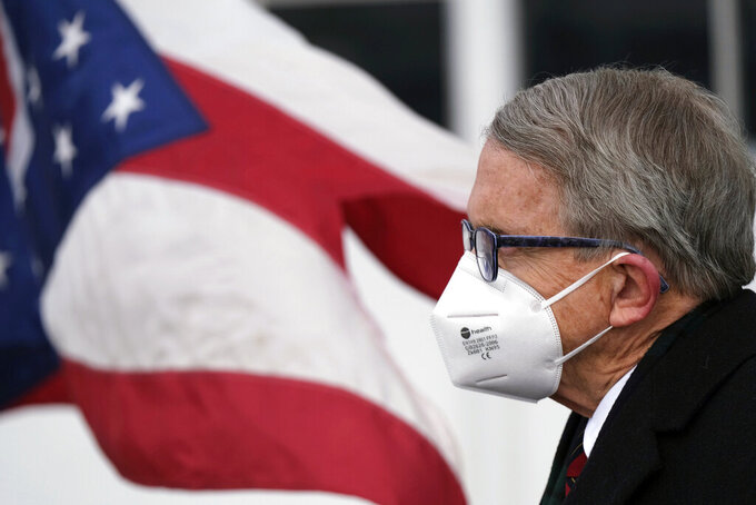 FILE - In this Wednesday, Nov. 18, 2020, file photo, Ohio Gov. Mike DeWine looks on during a news conference at Toledo Express Airport in Swanton, Ohio. On Thursday, Dec. 3, 2020, DeWine announced that Ohio will receive close to 100,000 doses of the coronavirus vaccine by mid-December. The brief but promising details provided the first look at what vaccine distribution will look like in the state as the number of cases, deaths and hospitalizations continue to rise at staggering rates. (J.D. Pooley/Sentinel-Tribune via AP, File)