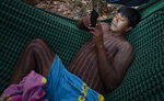 A Kayapo Indigenous man checks his cellphone while resting in a hammock after the temporary suspension of a protest where his group blocked Highway BR-163 near Novo Progresso, Para state, Brazil, Wednesday, Aug. 19, 2020. Indigenous leaders said they will block the highway again the next day to pressure Brazilian President Jair Bolsonaro to better shield them from COVID-19, to extend damages payments for road construction near their land, and to consult them on a proposed cargo railway. (AP Photo/Andre Penner)