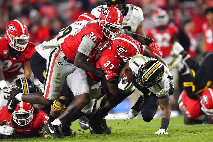 Georgia linebacker Tae Crowder (30) and linebacker Robert Beal Jr. (33) bring down Missouri running back Tyler Badie during the second half of an NCAA college football game Saturday, Nov. 9, 2019, in Athens, Ga. (AP Photo/John Amis)