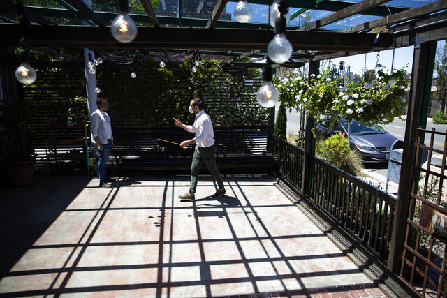 Co-owners Niccolo Angius, right, and Giuseppe Capasso measure available space in their outdoor seating area as they devise a plan to reopen their Cesarina restaurant Tuesday, May 12, 2020, once it is allowed by local authorities in San Diego. California is recommending restaurants screen guests for symptoms, have servers wear masks and keep diners at least six feet (1.8 meters) apart o prevent the spread of the coronavirus once they reopen. (AP Photo/Greg Bull)