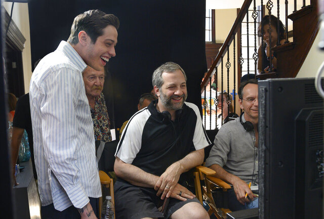 In this image released by Universal Pictures, Pete Davidson, left, appears with director Judd Apatow, center, during the filming of