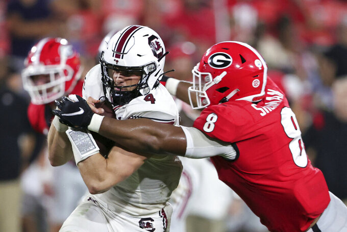 """FILE - South Carolina quarterback Luke Doty (4) is tackled by Georgia linebacker MJ Sherman (8) during the second half of an NCAA college football game in Athens, Ga., in this Saturday, Sept. 18, 2021, file photo. Georgia won 40-13. The depth of No. 2 Georgia's defense made South Carolina coach Shane Beamer feel like he was dealing with """"100 5-star football players on their defense."""" (AP Photo/Butch Dill, File)"""
