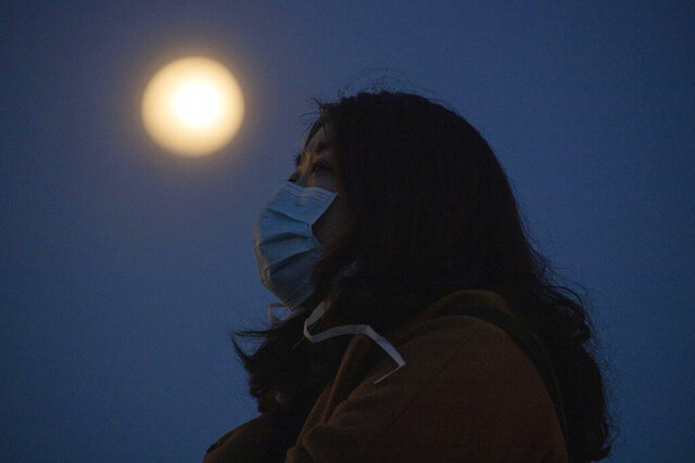 In this Monday, April 6, 2020, photo, a woman wearing a mask against the coronavirus looks up near the full moon in Wuhan in central China's Hubei province. When the Chinese city of Wuhan is at last released from virus quarantine Wednesday, it will be like awakening from a persistent slumber. Over the 76 days of lockdown, the city has at times lived in a crepuscular world of neither night or day, where time seems to pass more slowly and one day blurs into the next. (AP Photo/Ng Han Guan)