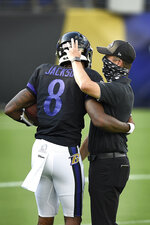 "FILE - Baltimore Ravens quarterback Lamar Jackson, left, hugs head coach John Harbaugh during an NFL football training camp practice, Saturday, Aug. 29, 2020, in Baltimore, Md. They'll be playing Sunday in an empty stadium, facing a Cleveland Browns team with a new coaching staff that's provided no clue how they plan to employ a revamped offense. ""A lot of unknowns,"" Ravens coach John Harbaugh acknowledged. About the only thing for sure is that Baltimore quarterback Lamar Jackson, the multi-faceted reigning NFL MVP, will be the focal point of an offense that last year set a league record with 3,296 yards rushing and helped the Ravens win the AFC North with the best regular-season record in the NFL. (AP Photo/Gail Burton, FIle)"