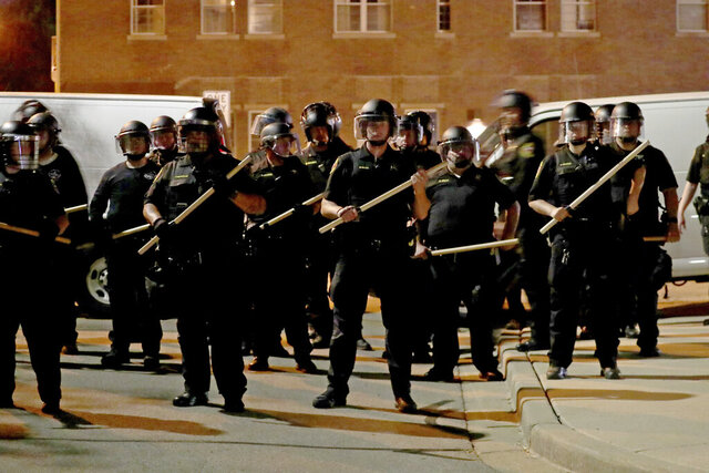 FILE - In this Aug. 23, 2020 file photo, police in riot gear stand guard in Kenosha, Wis. According to police officials, two police officers who were on the scene when a white officer shot and partially paralyzed a Black man in Wisconsin, triggering several nights of violent protests, have returned to duty. The update announced Wednesday, Jan. 27, 2021, comes as Officer Rusten Sheskey, who shot Jacob Blake seven times on Aug. 23, in Kenosha, remains on administrative leave while a police review board examines the case.  (Mike De Sisti/Milwaukee Journal-Sentinel via AP, File)