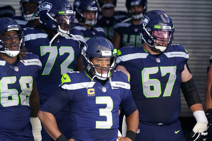 Seattle Seahawks quarterback Russell Wilson (3) stands with teammates in the tunnel before an NFL football game against the Dallas Cowboys, Sunday, Sept. 27, 2020, in Seattle. (AP Photo/Elaine Thompson)