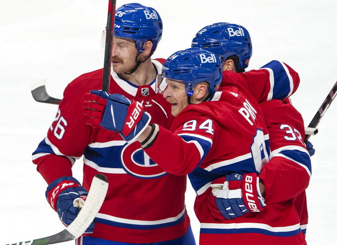 Montreal Canadiens' Corey Perry (94) celebrates his goal with teammates Jeff Petry (26) and Eric Gustafsson (32) during the first period of an NHL Stanley Cup playoff hockey game against the Winnipeg Jets, in Montreal, Sunday, June 6, 2021. (Ryan Remiorz/The Canadian Press via AP)