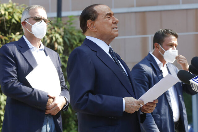 FILE - In this Monday, Sept. 14, 2020 file photo, Silvio Berlusconi is flanked by his personal physician Alberto Zangrillo, left, as he talks to the media while leaving the San Raffaele hospital in Milan, Italy. Former Italian Premier Silvio Berlusconi is hospitalized in the principality of Monaco for medical tests for heart problems, his press office confirmed on Thursday, Jan. 14, 2021. The 84-year-old three-time premier is expected to return home in a few days. (AP Photo/Luca Bruno, File)