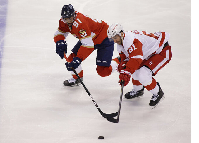 Florida Panthers left wing Anthony Duclair (91) and Detroit Red Wings Frans Nielsen (81) battle for the puck during the second period of an NHL hockey game on Tuesday, March 30, 2021, in Sunrise, Fla. (AP Photo/Terry Renna)
