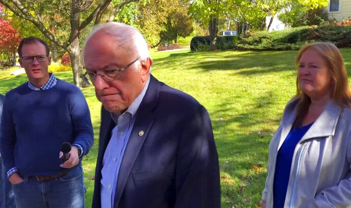 In this image taken from video, Democratic presidential candidate Sen. Bernie Sanders, I-Vt., speaks we reporters outside his home, Tuesday, Oct. 8, 2019, in Burlington, Vt. His wife, Jane O'Meara Sanders listens at right. Sanders says he was