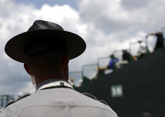 FILE - In this Thursday, June 12, 2014 file photo, a North Carolina State Trooper stands guard during the U.S. Open golf tournament in Pinehurst, N.C. On Tuesday, Feb. 18, 2020, an appeals court ruled that a former Trooper Thomas Wetherington shouldn't have been fired for losing his hat in 2009 and lying about it in a case that's spanned a decade and multiple trips through the courts. (AP Photo/David Goldman)
