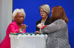 Broward County Supervisor of Elections Brenda Snipes, left, Board chair Judge Betsy Benson, center, and Board member Judge Deborah Carpenter-Toye, sign off on a sealed bin that will be sent to the capitol as ballots have begun to be sorted before counting, Monday, Nov. 12, 2018, in Lauderhill, Fla. (AP Photo/Wilfredo Lee)