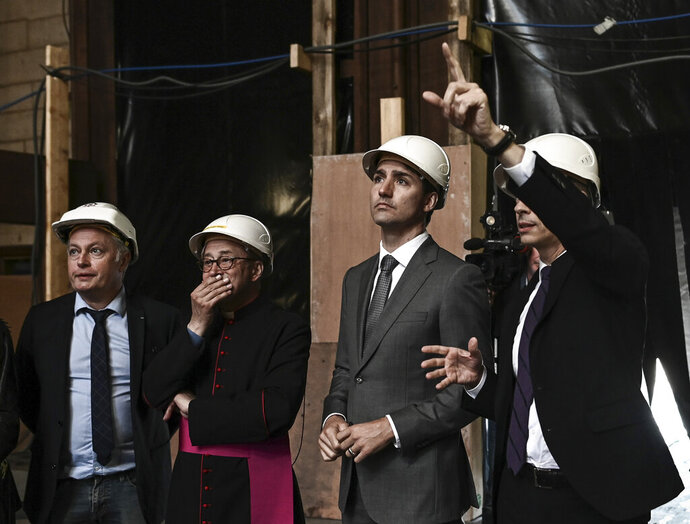 Canadian Prime Minister Justin Trudeau, third left, French Culture Minister Franck Riester, right, Notre Dame cathedral rector Patrick Chauvet, second left, and French chief architect of Historical Sites Philippe Villeneuve visit the Notre Dame de Paris cathedral, Wednesday May 15, 2019 in Paris. (Philippe Lopez/Pool via AP)