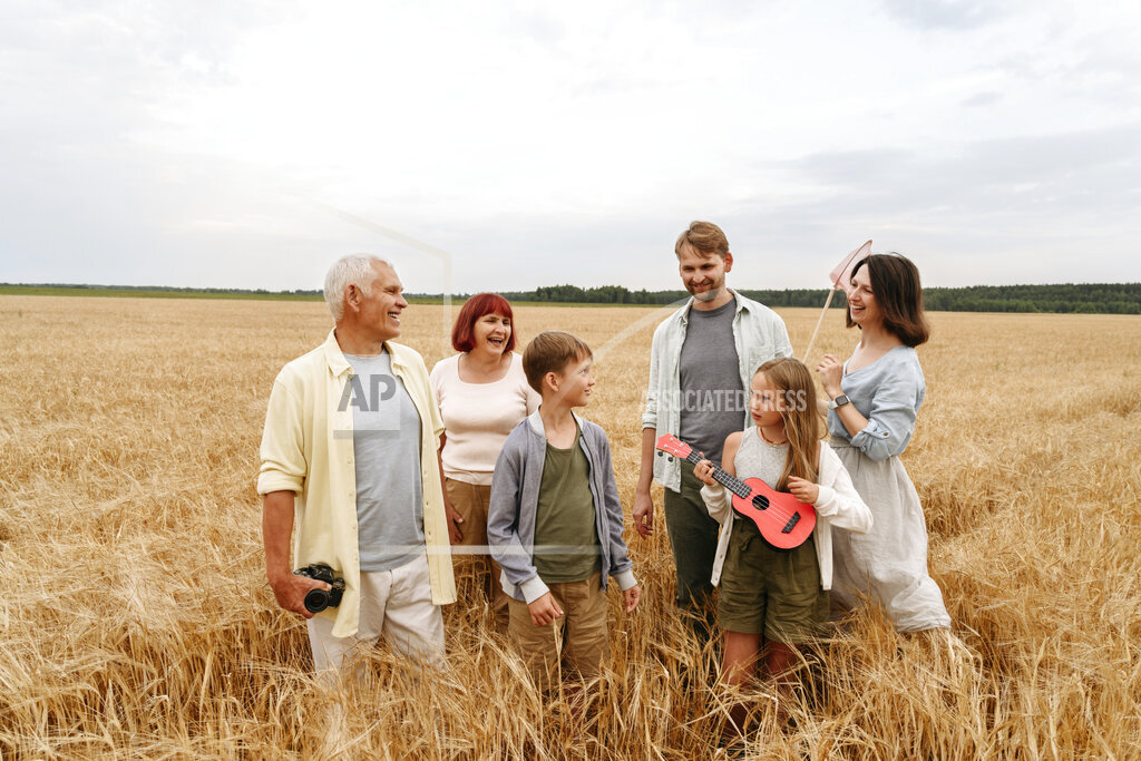 Happy family standing together in wheat field