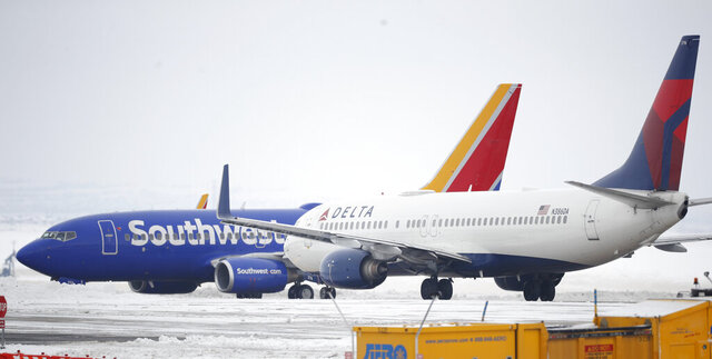 A Delta Airlines jetliner waits for a Southwest jetliner to taxi pst on the way to a runway for take off from Denver International Airport as travelers deal with the spread of coronavirus Friday, March 20, 2020, in Denver. According to the World Health Organization, most people recover in about two to six weeks depending on the severity of the COVID-19 illness. (AP Photo/David Zalubowski)