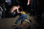 Men lie on the ground during Algerian rap artist Abderraouf Derradji's concert, known as Soolking, at a stadium in Algiers, Thursday, Aug. 22, 2019. The concert caused some deaths and injuries in a stampede as fans thronged an entrance at the rap concert in the Algerian capital. (AP Photo/Fateh Guidoum)