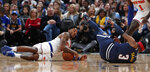 New York Knicks guard Elfrid Payton, left, recovers a loose ball as Denver Nuggets forward Torrey Craig falls on the court in the second half of an NBA basketball game Sunday, Dec. 15, 2019, in Denver. The Nuggets won 111-105. (AP Photo/David Zalubowski)
