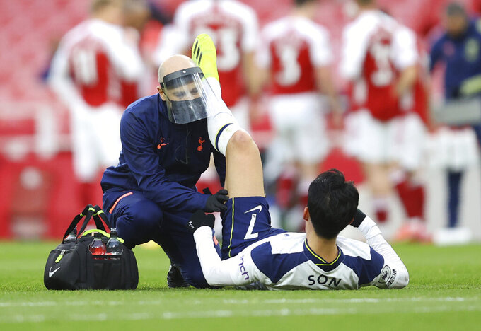 Tottenham's Son Heung-min receives medical attention during the English Premier League soccer match between Arsenal and Tottenham Hotspur at the Emirates stadium in London, England, Sunday, March 14, 2021. (Julian Finney/Pool via AP)