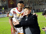 Catalans Dragons Israel Folau has his photo taken with a young fan after the Super League rugby match between Catalans Dragons and Castleford Tigers at Stade Gilbert Brutus in Perpignan, France, Saturday, Feb. 15, 2020. (AP Photo/Joan Monfort)
