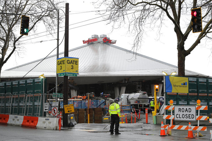 In this March 30, 2020, photo, KeyArena is shown with renovation construction resumed after being temporarily halted due to the outbreak of the coronavirus. The pandemic has created questions of scheduling and worker health as eight stadiums or arenas are under construction or about to break ground in the five major professional sports leagues in North America. The facility is the home of the WNBA Seattle Storm, and will be the home of Seattle's expansion NHL team, which is scheduled to begin play in the 2021-22 season. (AP Photo/Ted S. Warren)