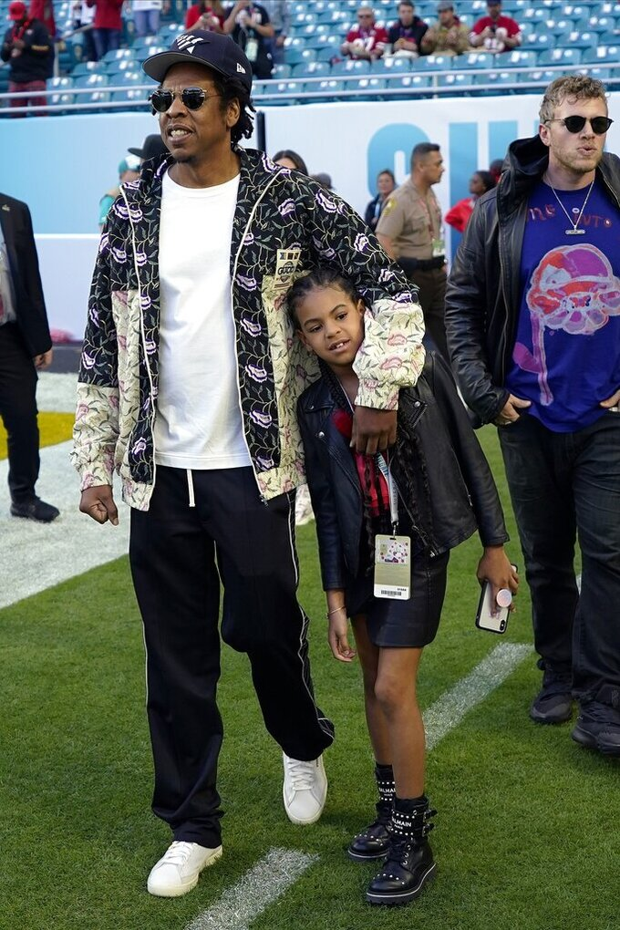Entertainer Jay-Z walks with his daughter Blue Ivy Carter as they arrive for the NFL Super Bowl 54 football game between the San Francisco 49ers and the Kansas City Chiefs, Sunday, Feb. 2, 2020, in Miami. (AP Photo/David J. Phillip)