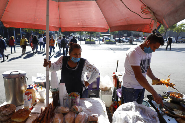 Lourdes Sanvicente, 45, left, and a coworker wear protective face masks at the direction of the stand's owner, as they sell tamales, sandwiches, and pastries at a street stand in Mexico City, Wednesday, March 25, 2020. Sanvicente, who doubts the existence of the new coronavirus, says both she and her husband work as street food sellers, together earning 320 pesos (around $13.50) per day to support themselves and their five children.