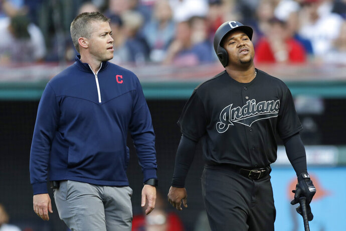 Cleveland Indians' Jose Ramirez, right, walks off the field with a trainer during the first inning of the team's baseball game against the Kansas City Royals, Saturday, Aug. 24, 2019, in Cleveland. (AP Photo/Tony Dejak)