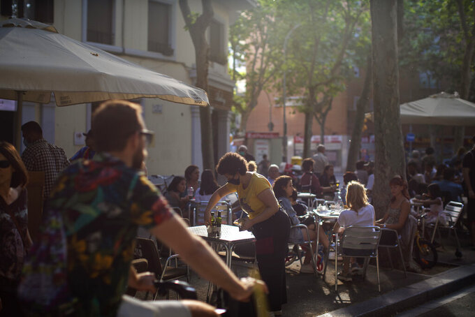 Customers sit at a terrace bar in Barcelona, Spain, Sunday, May 31, 2020. Spanish Prime Minister Pedro Sánchez says he will ask Spain's Parliament for a final two-week extension of the nation's state of emergency that has allowed the government to take lockdown measures to control its coronavirus outbreak. (AP Photo/Emilio Morenatti)
