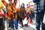 Gun rights activist Deserae Morin, with seven-year old daughter Maple, facing center, shouts as Vermont Republican Gov. Phil Scott speaks before signing the first significant gun restrictions bills in the state's history during a ceremony on the steps of the Statehouse in Montpelier, Vt., Wednesday, April 11, 2018. (AP Photo/Cheryl Senter)