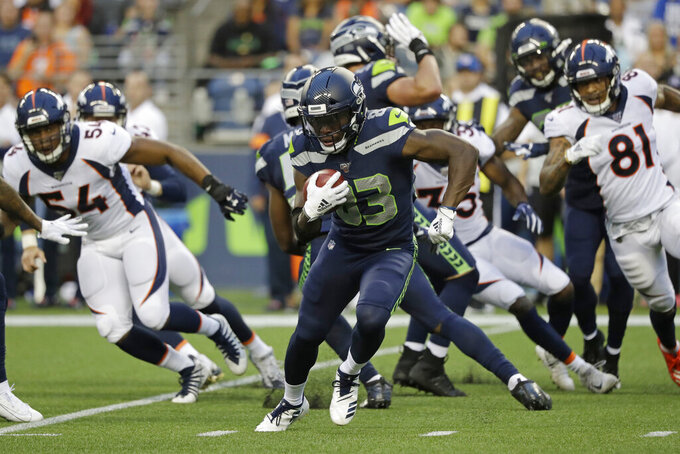 Seattle Seahawks' David Moore (83) carries the ball against the Denver Broncos during the first half of an NFL football preseason game Thursday, Aug. 8, 2019, in Seattle. (AP Photo/Elaine Thompson)