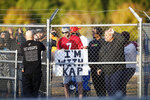 Fans watch from behind a fence as free agent quarterback Colin Kaepernick participates in a workout for NFL football scouts and media, Saturday, Nov. 16, 2019, in Riverdale, Ga. (AP Photo/Todd Kirkland)
