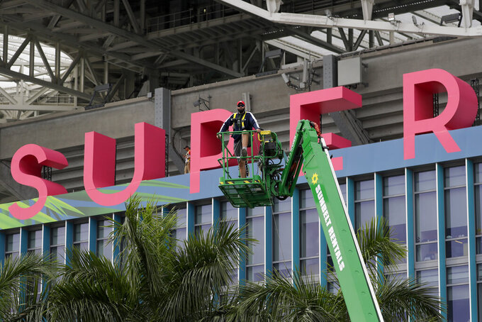 A worker strings wire outside of the Hard Rock Stadium Monday, Jan. 27, 2020, in Miami Gardens, Fla. in preparation for the NFL Super Bowl 54 football game. (AP Photo/Chris Carlson)