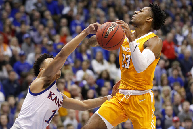 Kansas guard Devon Dotson (1) knocks the ball away from Tennessee guard Jordan Bowden (23) during the second half of an NCAA college basketball game in Lawrence, Kan., Saturday, Jan. 25, 2020. Kansas defeated Tennessee 74-68. (AP Photo/Orlin Wagner)