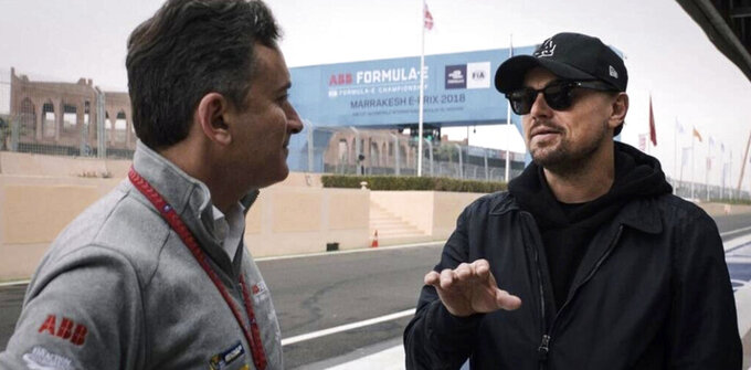 "In this handout provided by Formula E Operations Limited, Alejandro Agag, left, and Leonardo DiCaprio appear in a scene from the film ""And We Go Green."" (Malcolm Venville, Formula E Operations Limited via AP)"