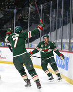 Minnesota Wild left wing Zach Parise, right, and center Nico Sturm celebrate after Parise scored a goal against the San Jose Sharks during the first period of an NHL hockey game Saturday, April 17, 2021, in St. Paul, Minn. (AP Photo/Craig Lassig)