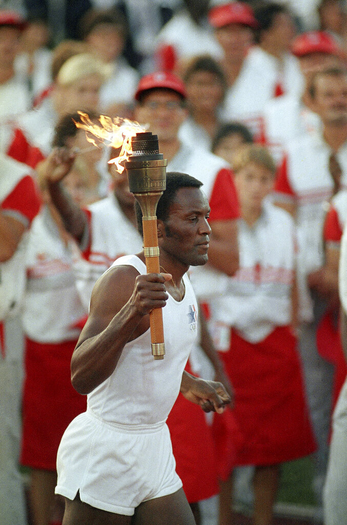 FILE -  In this July 28, 1984, file photo, 1960 U.S. gold medal decathlete Rafer Johnson carries the Olympic torch through the Los Angeles Memorial Coliseum before lighting the Olympic flame and formally launching the 1984 summer games. Rafer Johnson died Wednesday, Dec. 2, 2020. He was 86. He died at his home in the Sherman Oaks section of Los Angeles, according to family friend Michael Roth. (AP Photo/Peter Leabo, File)