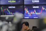 A currency trader watches computer monitors at the foreign exchange dealing room in Seoul, South Korea, Friday, Nov. 29, 2019. Shares extended losses in Asia on Friday after Japan and South Korea reported weak manufacturing data that suggest a worsening toll from trade tensions. (AP Photo/Lee Jin-man)