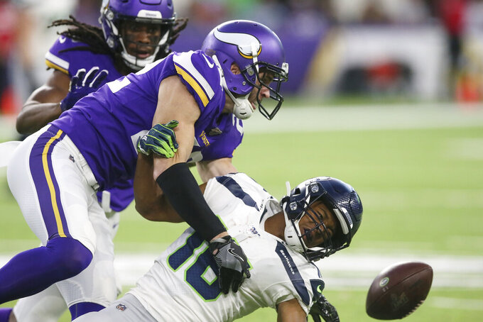 Minnesota Vikings free safety Harrison Smith, left, breaks up a pass intended for Seattle Seahawks wide receiver Tyler Lockett (16) during the first half of an NFL preseason football game, Sunday, Aug. 18, 2019, in Minneapolis. (AP Photo/Jim Mone)