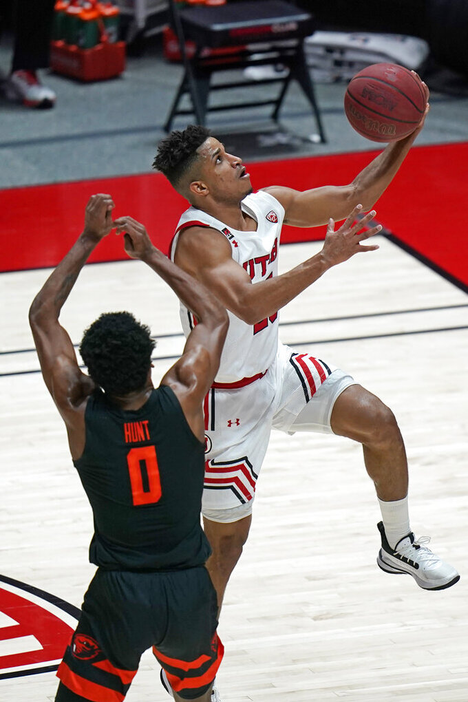 Utah guard Alfonso Plummer, rear, lays the ball up as Oregon State guard Gianni Hunt (0) defends during the first half of an NCAA college basketball game Wednesday, March 3, 2021, in Salt Lake City. (AP Photo/Rick Bowmer)